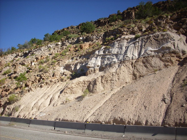 Road cut in Bandelier Tuff highlighting zeolitized zones